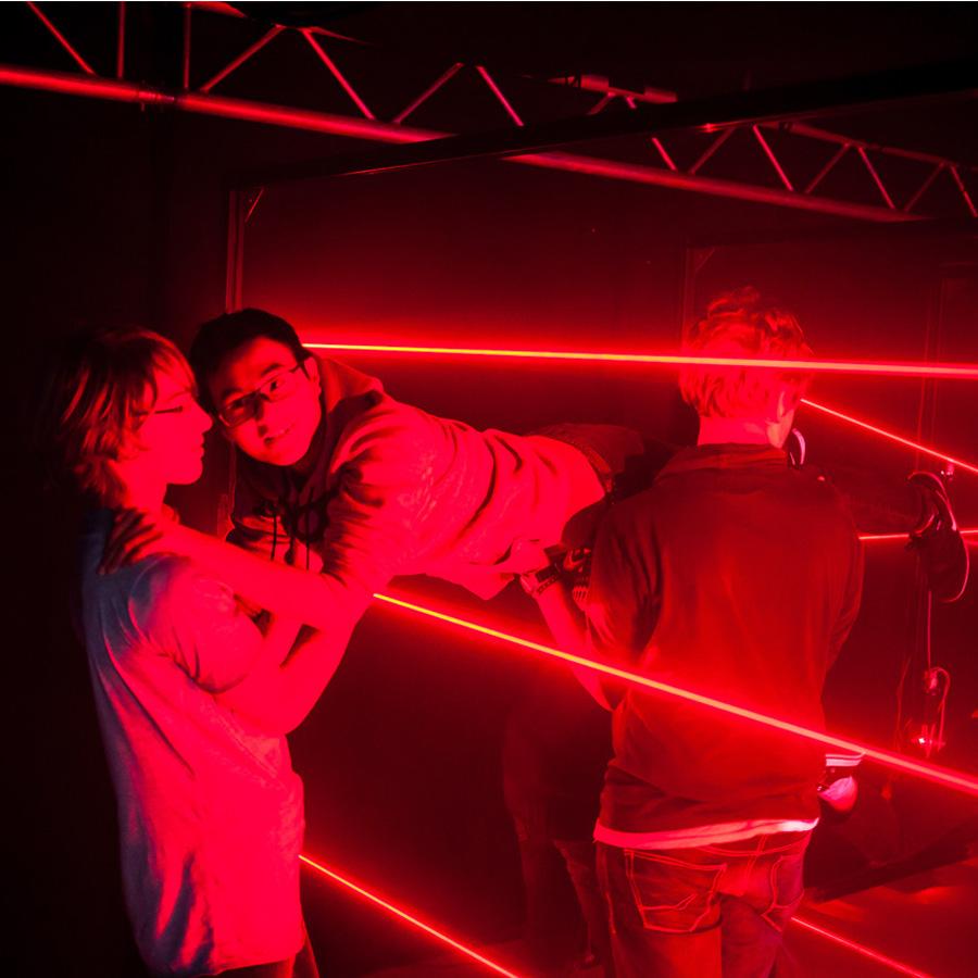 Teammitglieder helfen sich gegenseitig den Laser Maze zu durchqueren